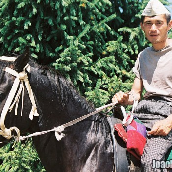 Photo of Man with paper hat riding a horse in Medeu Mountains, Kazakhstan - Central Asia