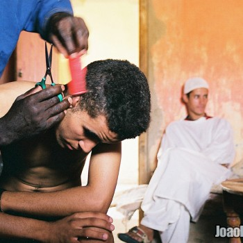 Man cutting the other one's hair in Erg Chebbi Dunes, Sahara Desert South-East Morocco