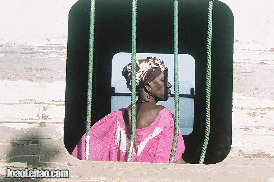 Photo of Woman looking out the window in ferry-boat from Banjul to Barra, The Gambia West Africa