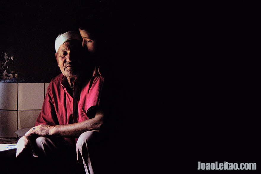 Photo of grandfather and grandson inside dark room in Taddert village, High Atlas Mountains, Morocco - North Africa