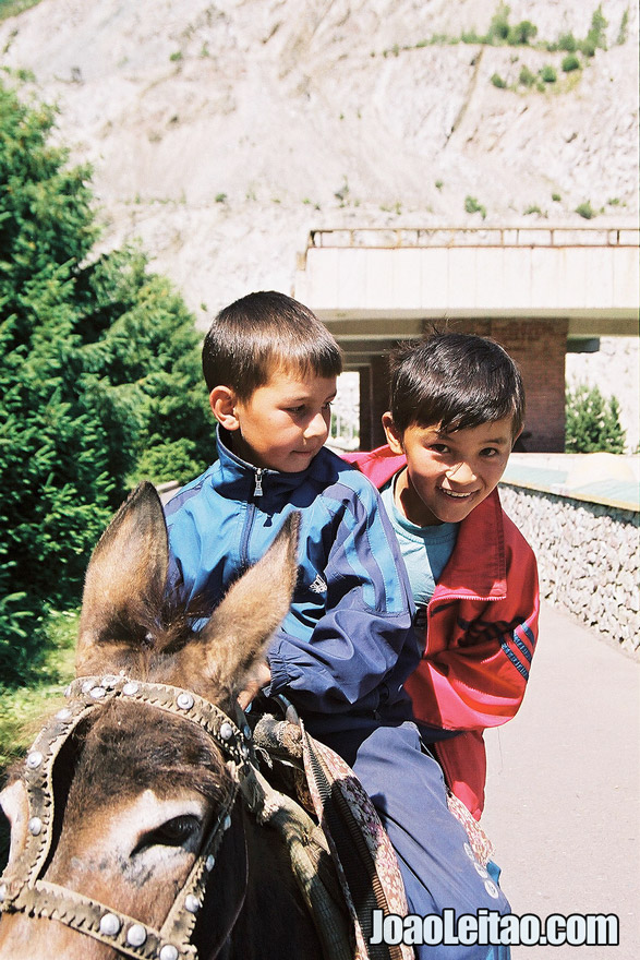 Photo of Boys riding a donkey in Medeu Mountains, Kazakhstan - Central Asia