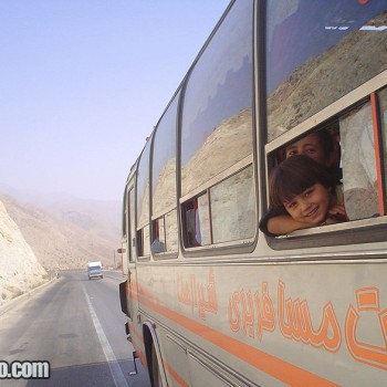 Photo of Iranian children looking through the window in bus from Bandar-e Abbas to Shiraz, Zagros Mountains, Iran - Middle East